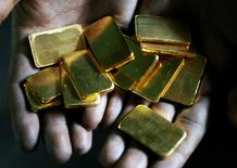 FILE PHOTO: A worker shows gold biscuits at a precious metals refinery in Mumbai, India March 3, 2008. REUTERS/Arko Datta/File Photo