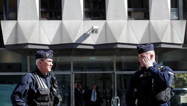 3月16日、パリの国際通貨基金(IMF)の事務所で郵便物が爆発し、開封していた女性職員が顔や腕に火傷を負った。IMFには最近脅迫電話が相次いでいたが、この日の爆発と関連があるかは不明という。犯行声明は出されていない。写真は同日、爆発があったパリのIMFの事務所が入るビルの中央出入り口前(2017年 ロイター/Christian Hartmann)