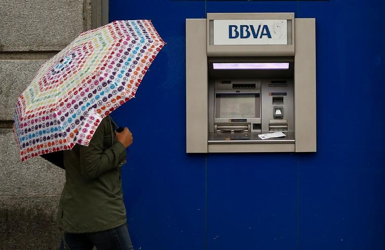 A woman with an umbrella walks past a BBVA bank branch in central Madrid, Spain, April 4, 2016. REUTERS/Andrea Comas/File Photo