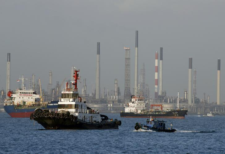 Vessels pass an oil refinery in the waters off the southern coast of Singapore, February 26, 2016. REUTERS/Edgar Su/File Photo