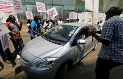 Kenyan taxi drivers signed up to ride-hailing service Uber attempt to eject a passenger from one of the Uber operating taxis during a strike after the company slashed prices in the face of growing competition from similar local firms in Kenya's capital Nairobi, August 2, 2016. REUTERS/Thomas Mukoya
