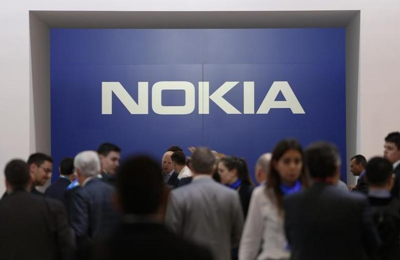 Visitors stand next to a logo of Nokia at Mobile World Congress in Barcelona, Spain, February 27, 2017. REUTERS/Paul Hanna
