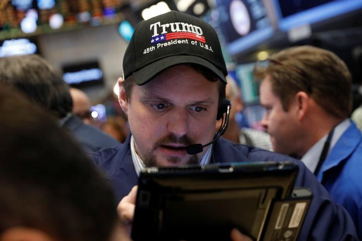 A trader wears a Donald Trump hat while working on the floor of the New York Stock Exchange (NYSE) shortly after the opening bell in New York, U.S., March 16, 2017.  REUTERS/Lucas Jackson