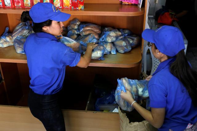 Saleswomen grab bags of bread at a bakery in Caracas, Venezuela March 17, 2017. REUTERS/Marco Bello
