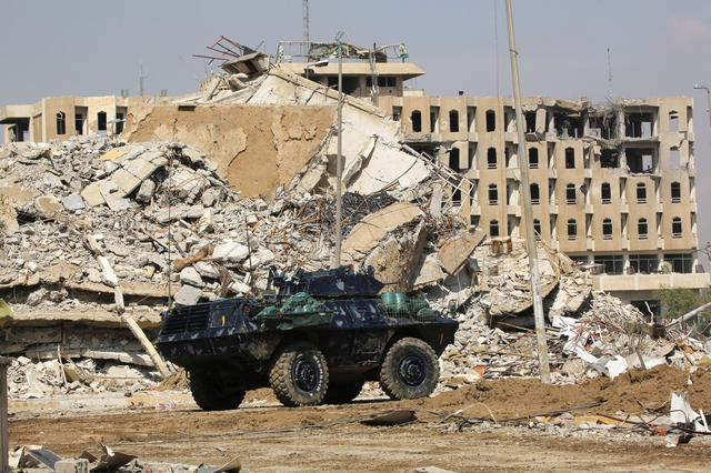 An armored vehicle of federal police drives past destroyed buildings from clashes during a battle against Islamic State militants at the Bab al-Tob area in Mosul. REUTERS/Ari Jalal