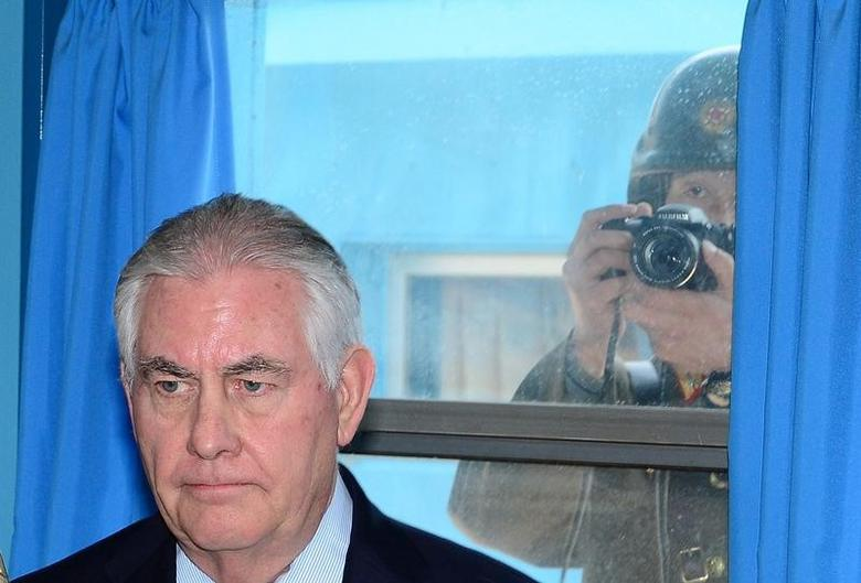 U.S. Secretary of State Rex Tillerson is briefed by U.S. Gen. Vincent K. Brooks, commander of the United Nations Command, Combined Forces Command and United States Forces Korea (not pictured), as a North Korean soldier takes a photograph through a window at the border village of Panmunjom, South Korea, March 17, 2017. Korea Pool/Yonhap via REUTERS