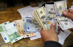"""Сотрудник пункта обмена валют в Каире пересчитывает доллары и евро. Доллар снизился на азиатских торгах понедельника на фоне сохранения разочарования """"быков"""" в связи с более миролюбивой, чем многие ждали, риторикой Федрезерва на прошлой неделе.   REUTERS/Mohamed Abd El Ghany"""