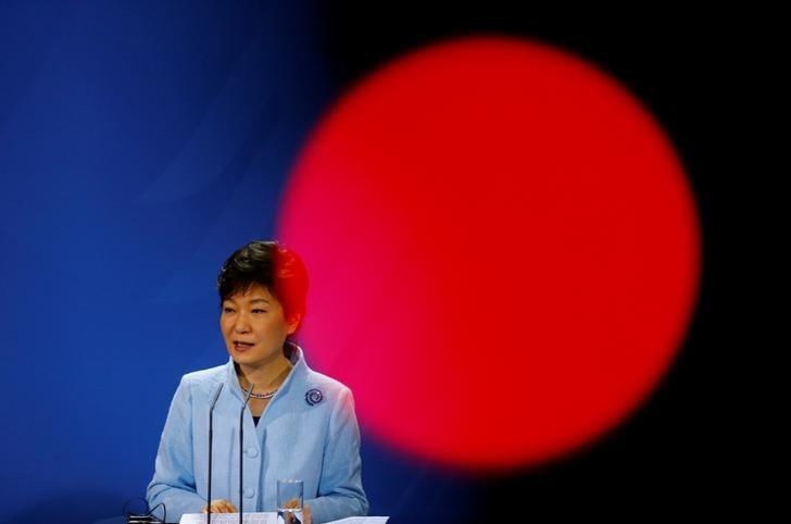 South Korean President Park Geun-hye addresses a joint news conference with German Chancellor Angela Merkel (not pictured) at the Chancellery in Berlin March 26, 2014. Red circle is from a light on a TV camera.     REUTERS/Kai Pfaffenbach/Files