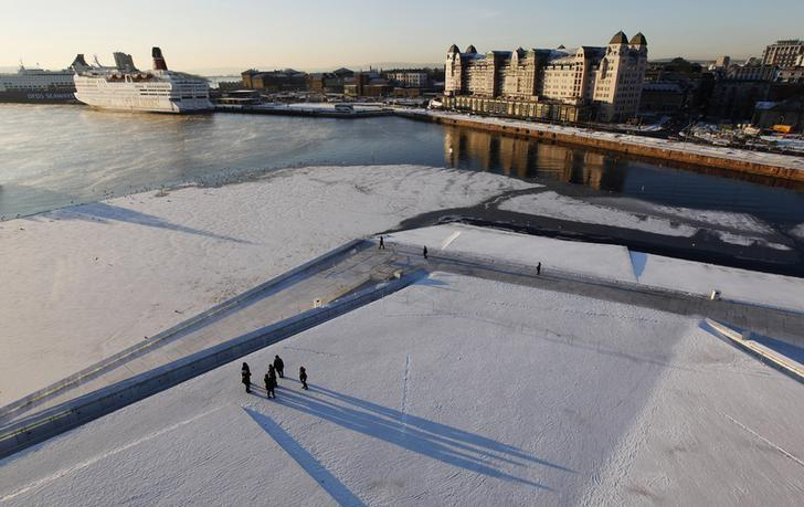 Pedestrians walk by the harbour during winter in Oslo December 11, 2012. REUTERS/Suzanne Plunkett (NORWAY - Tags: MARITIME CITYSCAPE ENVIRONMENT)