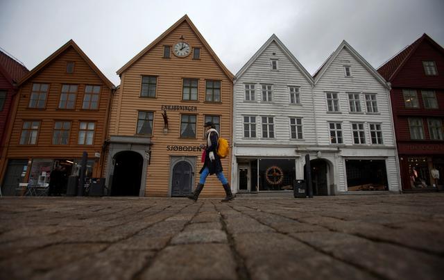 A woman walks near Bryggen (the Wharf) near the marina in downtown Bergen. REUTERS/Stoyan Nenov