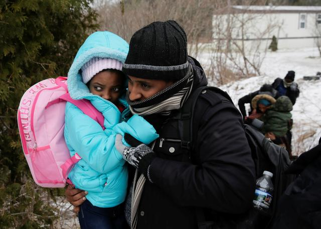 A group that claimed to be from Eritrea crosses the U.S.-Canada border into Hemmingford, Quebec. Security experts predict more will attempt to enter Canada as the snow melts and the weather warms. REUTERS/Dario Ayala