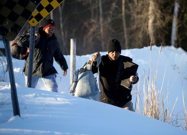 A man who claimed to be from Sudan climbs over a pile of snow as he and his family illegally cross the U.S.-Canada border leading into Hemmingford, Quebec, Canada, March 20, 2017. REUTERS/Christinne Muschi