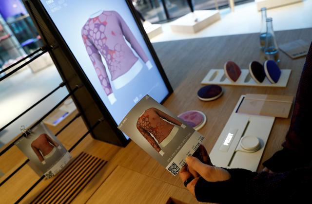 A staff shows the print of a knitting pattern during the measuring process on a computer screen to order the knitting pattern at the Adidas knit for you store in Berlin, Germany March 7, 2017. REUTERS/Fabrizio Bensch