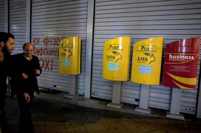 People make their way past mailboxes outside a closed Hellenic Post branch in Athens, Greece, March 20, 2017. REUTERS/Alkis Konstantinidis