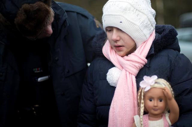 A young girl holding her doll cries as her family that claimed to be from Turkey are met by Royal Canadian Mounted Police (RCMP) officers after they crossed the U.S.-Canada border illegally leading into Hemmingford, Quebec Canada March 20, 2017.  REUTERS/Christinne Muschi