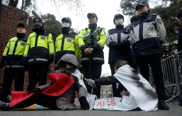 Supporters of South Korea's ousted leader Park Geun-hye sit on a road outside her private home in Seoul, South Korea, March 21, 2017, before Park Geun-hye heads to the prosecutors' office to be questioned over a widening corruption scandal.  Ahn Eun-Nah/NEWS 1 via REUTERS