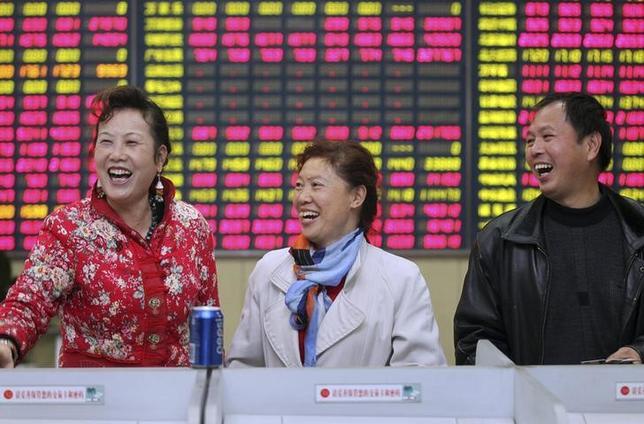 3月20日、中国政府が打ち出した香港─中国本土間の債券相互取引制度の導入計画は、香港にとって朗報だ。写真は江蘇省南通にある証券会社で笑顔を見せる投資家たち。2014年11月撮影(2017年 ロイター/China Daily)