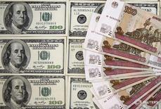 Рублевые и долларовые купюры в Сараево 9 марта 2015 года. Рубль приблизился к отметке 57 за доллар, переписывая одномесячные максимумы с оглядкой на снижение валюты США в паре с евро и текущий рост нефти, при этом на его стороне крупные налоговые выплаты текущего месяца и широкий дифференциал процентных ставок ФРС и ЦБР при большой вероятности сохранения российской ставки 10 процентов годовых на пятничном совете директоров Банка России. REUTERS/Dado Ruvic