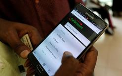 An employee assists a customer to set-up M-Pesa money transfer servive on his handset inside a mobile phone care centre operated by Kenyan's telecom operator Safaricom; in the central business district of Kenya's capital Nairobi, May 11, 2016. REUTERS/Thomas Mukoya