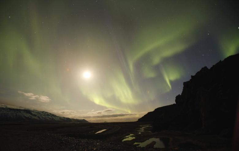 The Northern Lights are seen through a valley leading away from Iceland's Eyjafjallajokull volcano April 22, 2010.  REUTERS/Lucas Jackson