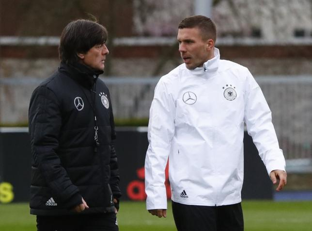 3月21日、サッカーのドイツ代表のヨアキム・レーウ監督(左)は、22日の国際親善試合イングランド戦が代表引退試合となるFWルーカス・ポドルスキ(右)を称賛した(2017年ロイター)