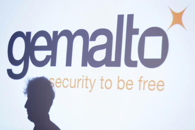 FILE PHOTO: The shadow of an attendee is cast below a logo of Franco-Dutch technology firm Gemalto during a news conference in Paris February 25, 2015. REUTERS/Gonzalo Fuentes