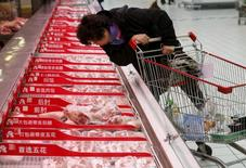 A customer chooses a meat product at Sun Art Retail Group's Auchan hypermarket store in Beijing, China, November 9, 2015. REUTERS/Kim Kyung-Hoon