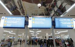 Travellers are seen at the Emirates terminal at Dubai International Airport, January 7, 2013. REUTERS/Jumana El Heloueh