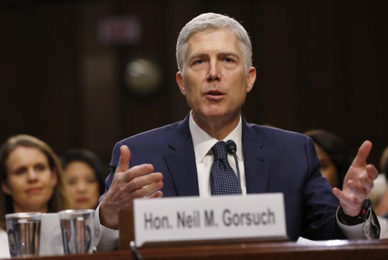FILE PHOTO: With his wife Marie Louise (L) looking on, U.S. Supreme Court nominee judge Neil Gorsuch testifies during a third day of his Senate Judiciary Committee confirmation hearing on Capitol Hill in Washington, U.S., March 22, 2017. REUTERS/Jonathan Ernst
