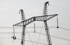 Рабочие на ЛЭП в Хакасии 1 июля 2012 года. Российский госоператор магистральных энергосетей ФСК увеличил чистую прибыль по международным стандартам в 2015 году на 55,1 процента до 68,4 миллиарда рублей. REUTERS/Ilya Naymushin