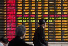 Инвесторы в Шанхае смотярт на табло с информацией о торгах. Фондовый рынок Китая слегка повысился по итогам торгов четверга, несмотря на падение шанхайских акций класса В из-за опасений по поводу нехватки ликвидности и усиления регулирования.  REUTERS/Aly Song  (CHINA - Tags: BUSINESS)