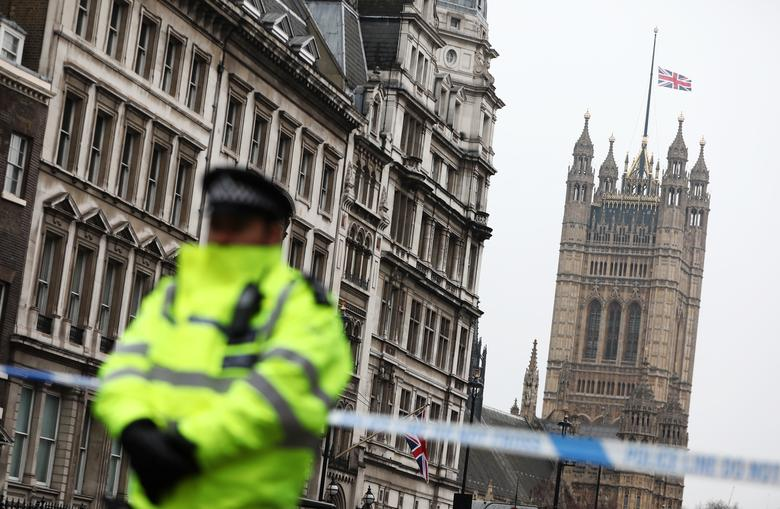 A police officer stands on duty as the union flag flies over Parliament at half-mast. REUTERS/Neil Hall