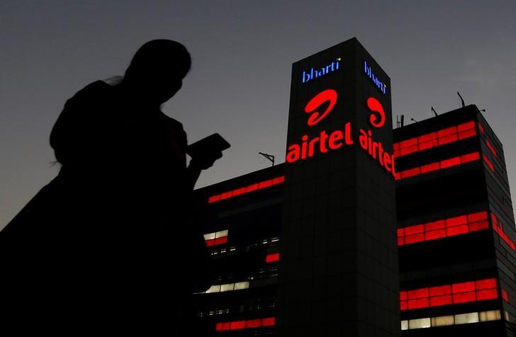 A girl checks her mobile phone as she walks past the Bharti Airtel office building in Gurugram, previously known as Gurgaon, on the outskirts of New Delhi, India April 21, 2016. REUTERS/Adnan Abidi/File Photo