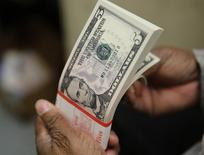 Um pacote de notas de cinco dólares dos Estados Unidos passa por inspeção 26/03/2015 REUTERS/Gary Cameron/File Photo