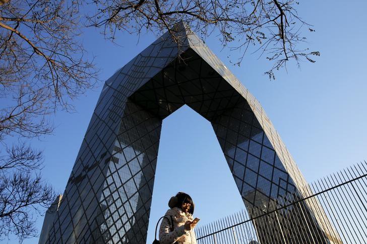 资料图片:2015年12月,北京一名上班族路过中国央视总部大楼。REUTERS/Damir Sagolj
