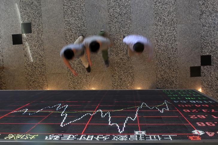 资料图片:2015年9月,中国上海,人们走过上海证交所股票信息显示屏下方。REUTERS/Aly Song