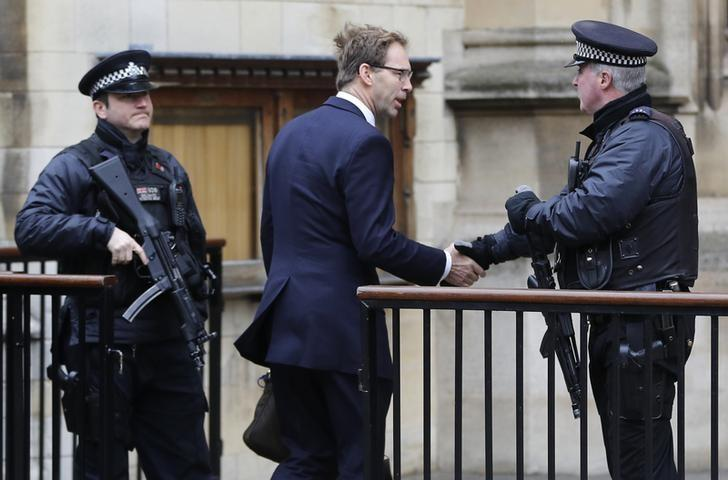 British Member of Parliament Tobias Ellwood shakes hands with an armed police officer as he arrives at the Houses of Parliament, following a recent attack in Westminster, London, Britain March 24, 2017.   REUTERS/Darren Staples