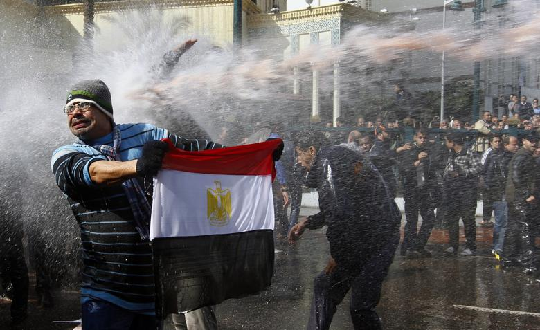 A protester holds an Egyptian flag as he stands in front of water canons during clashes in Cairo January 28, 2011. REUTERS/Yannis Behrakis