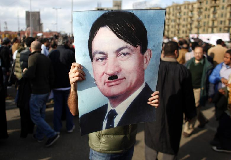 A man carries a picture depicting Egyptian President Hosni Mubarak as Adolf Hitler during a protest in Cairo January 31, 2011. REUTERS/Goran Tomasevic