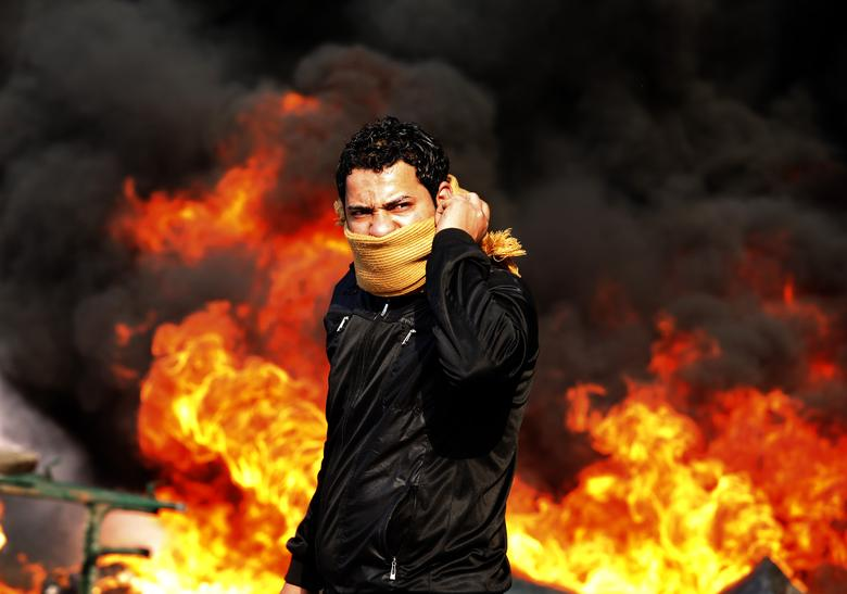 A protester stands in front of a burning barricade during a demonstration in Cairo January 28, 2011. REUTERS/Goran Tomasevic