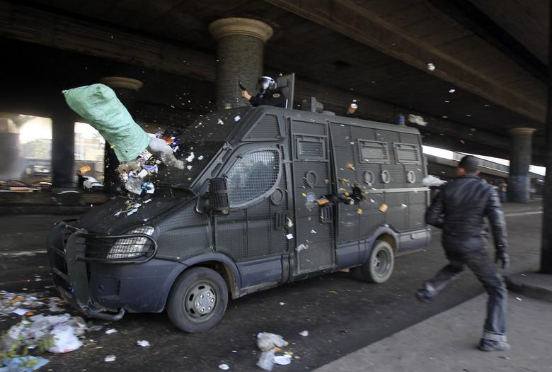 A protester runs next to a police vehicle after throwing a bag of trash at it during a demonstration in Cairo January 28, 2011. REUTERS/Goran Tomasevic