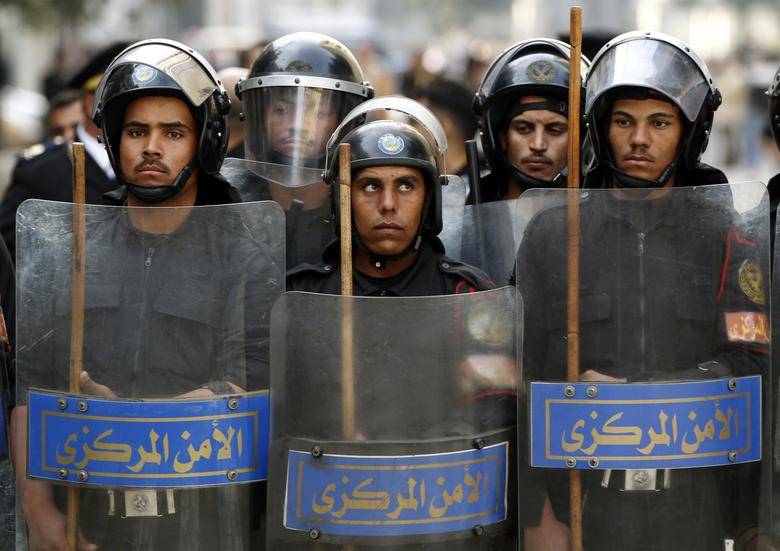 Riot police keep watch as they hold shields during clashes with protesters in Cairo January 26, 2011.REUTERS/Goran Tomasevic