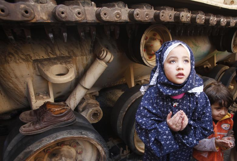 A girl attends Friday prayers in front of an army tank in Tahrir Square in Cairo February 18, 2011. REUTERS/Suhaib Salem