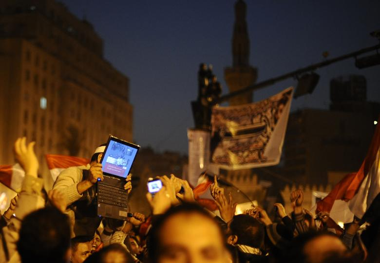 An opposition supporter holds up a laptop showing images of celebrations in Cairo's Tahrir Square, after Egypt's President Hosni Mubarak resigned February 11, 2011. REUTERS/Dylan Martinez