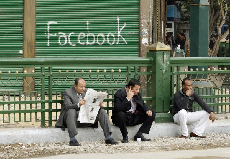 "Anti-government protesters sit next to a ""Facebook"" graffiti sign during demonstrations inside Tahrir Square in Cairo February 7, 2011. REUTERS/Dylan Martinez"