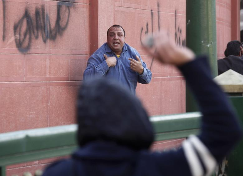 A man gestures as another throws a stone during clashes between pro and anti-Mubarak supporters clash at Tahrir Square in Cairo February 2, 2011. REUTERS/Goran Tomasevic