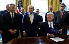 U.S. President Donald Trump smiles after announcing a permit for TransCanada Corp's Keystone XL oil pipeline while TransCanada Chief Executive Officer Russell Girling (L), U.S. Commerce Secretary Wilbur Ross (C) and Energy Secretary Rick Perry (R) stand beside him in the Oval Office of the White House in Washington, U.S., March 24, 2017. REUTERS/Kevin Lamarque