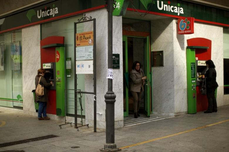 Women use ATM machines at a Unicaja bank branch at La Bola street in downtown Ronda, near Malaga January 29, 2014.   REUTERS/Jon Nazca