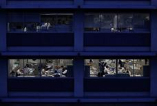 Office workers are pictured through building windows during dusk in Tokyo March 3, 2015.   REUTERS/Issei Kato/File Photo