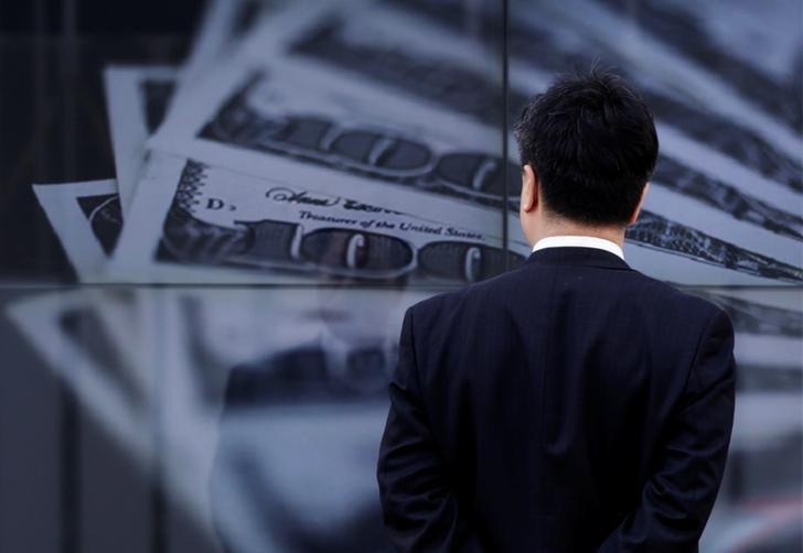 FILE PHOTO: A businessman looks at a screen displaying a photo of  U.S. 100 dollar bank notes in Tokyo April 8, 2013.  REUTERS/Toru Hanai/File Photo